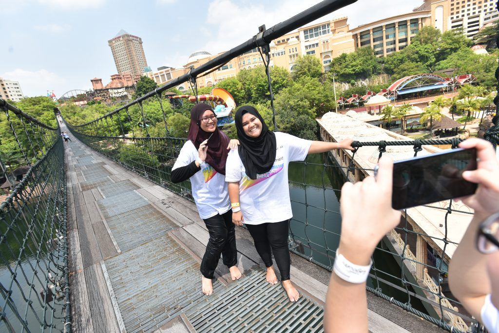 Media participants posing for a photo after completing a challenge on top of the Lagoon's Suspension Bridge.