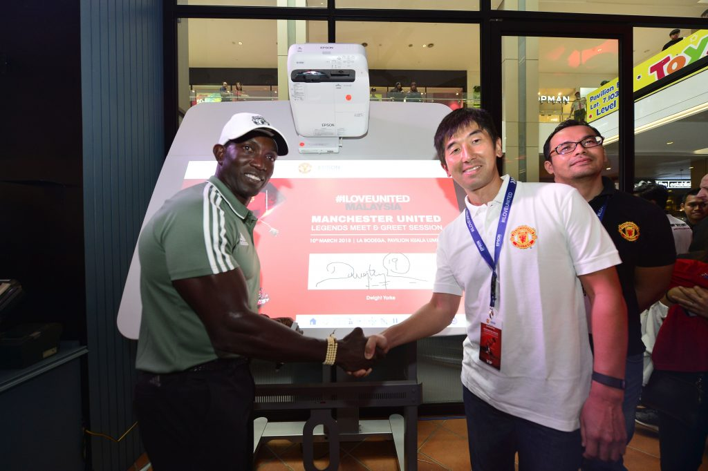 Daisuke Hori and Dwight Yorke shaking hands after the special signing on the Epson interactive projector