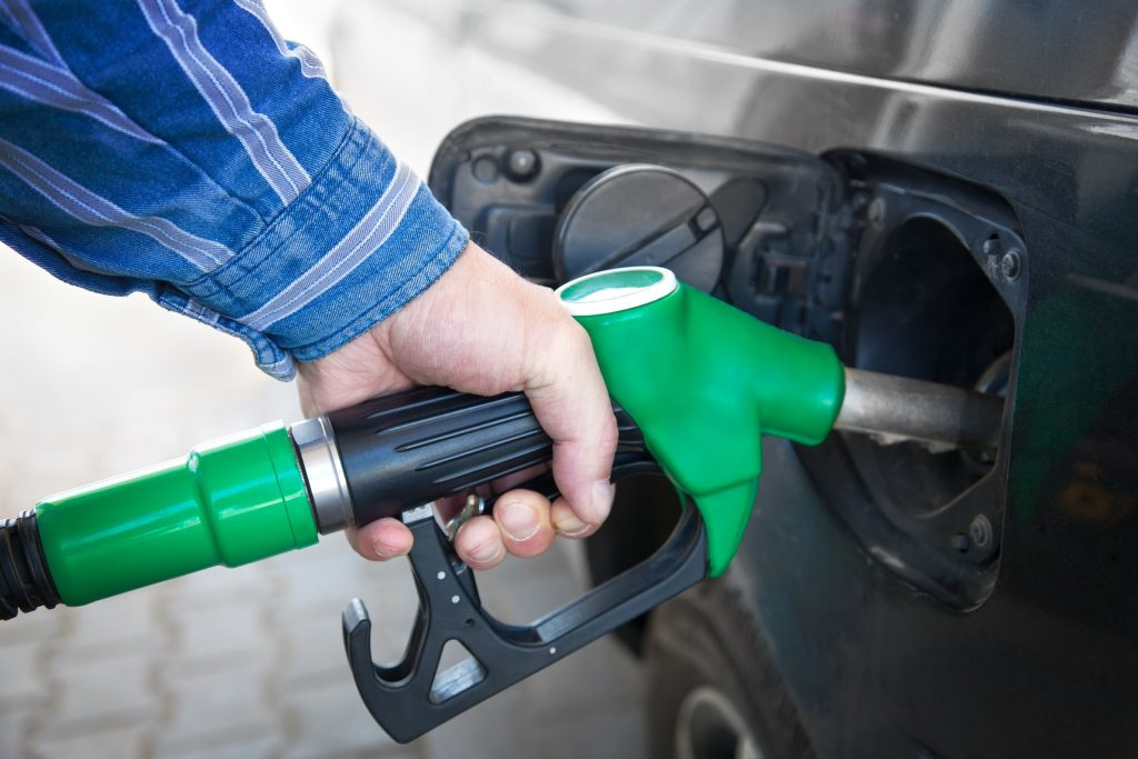 14697989 - male hand refilling the black car with fuel on a filling station