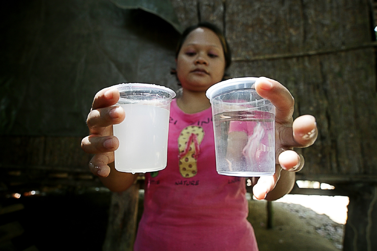 The Orang Asli villager showing the before and after results of water being filtered. Coway Malaysia is committed to providing safe and clean water for all Malaysians.