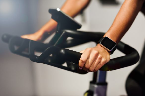 Hands of a woman training at a gym doing spinning or cyclo indoor with smart watch. Sports and fitness concept.